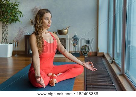 Portrait of pensive young woman meditating at home. She is sitting on floor in lotus position and looking out the window dreamingly