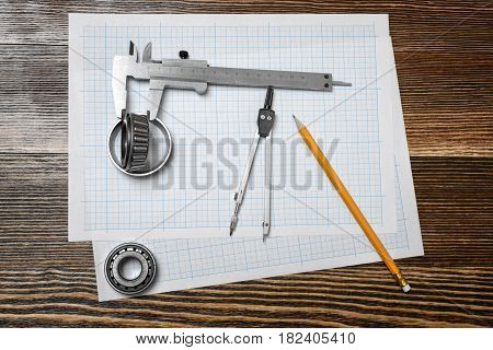 A vernier caliper holding a bearing, a pencil and a pair of compasses lying over drafting paper on wood background. Engineering and design. Repair works. Professional tools.