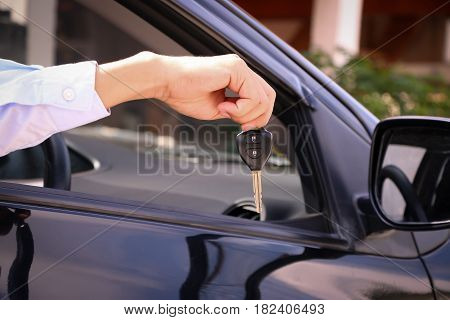 Business man smiling showing key and sit in car