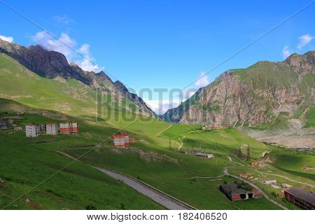 Russian Caucasus green mountains with old ruined houses