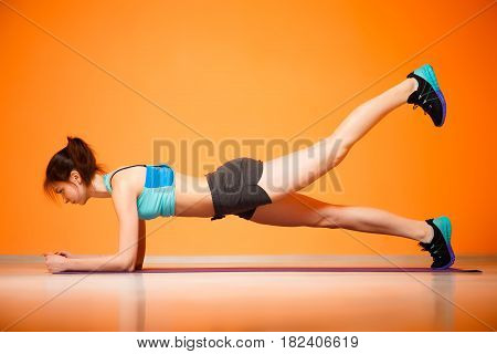 Young girl doing exercises on rug in gym