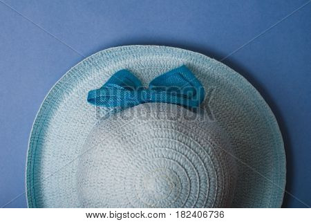 Beautiful summer hat of straw, on a blue background, a blue hat with bow