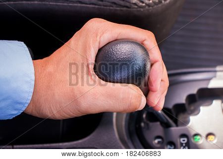 A business man holding gear in car.
