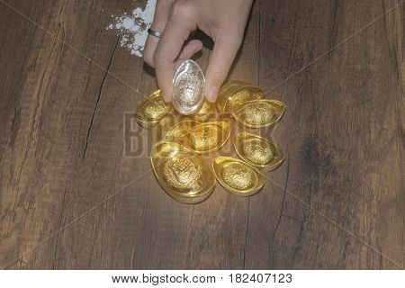 Decoration of chinese gold ingots in hand on wood backgroundTranslation in English meaning lucky and richly