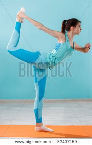 Young sportwoman doing yoga exercises on blue background