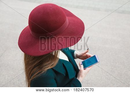 Woman in hat strolls around the city and uses her mobile phone. View from above