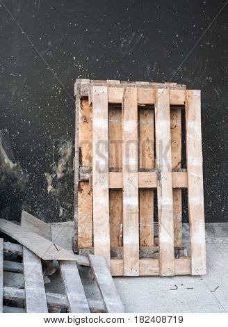 Broken wooden pallet near the unfinished house wall for used in the construction.