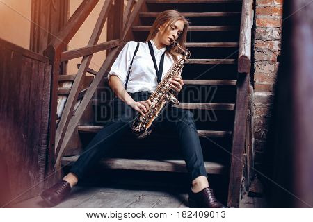 Beautiful young girl plays a saxophone sitting on steps - outdoors. Attractive woman in white shirt plays a saxophone.