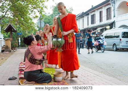 Luang Prabang, Laos - Mar 05 2015: Buddhist Monks Collecting Alms In The Morning. The Tradition Of G