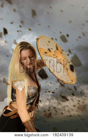 warrior woman using shield to block flying rocks