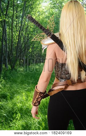 back of warrior woman walking in forest