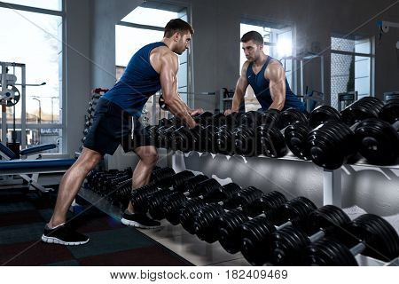 A sportive man in a T-shirt standing in front of a mirror takes dumbbells in the gym