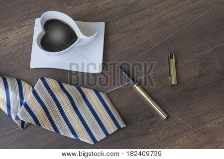 coffee and a striped tie on wooden background top view