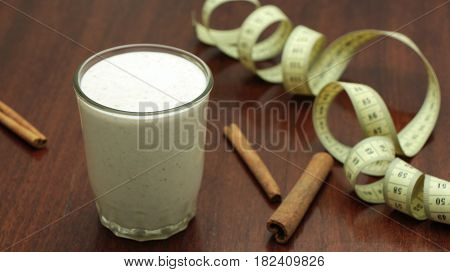Waight loss smoothie with cinnamon in a glass on wooden background