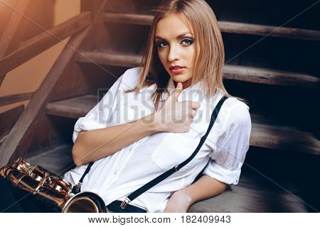 Young attractive girl sitting on steps in white shirt with a saxophone - outdoor in old town. Sexy young woman with sax looking at camera.