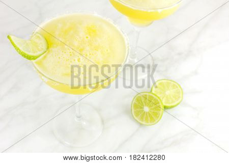A high key photo of lemon Margarita cocktails with wedges of lime, with a place for text. Selective focus