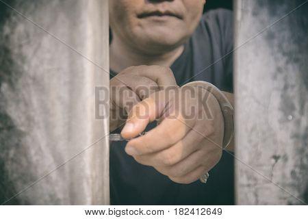 Human hand of prisoner on steel lattice close up. no freedom