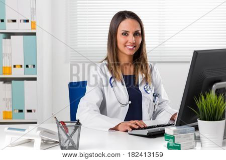 Female Doctor Sat At Desk Using Computer