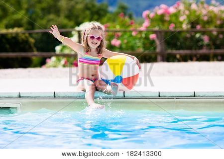 Little girl playing ball in outdoor swimming pool jumping into water on summer vacation on tropical beach island. Child learning to swim in pool of luxury resort. Water toy and sunglasses for kids.