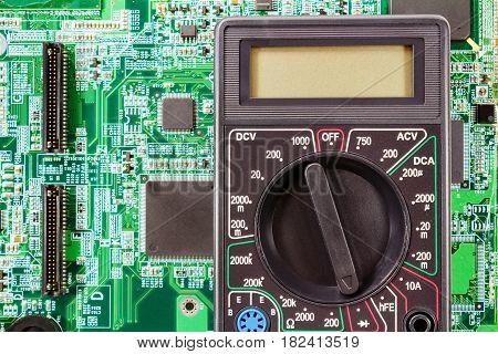 Digital multimeter on a printed circuit board closeup