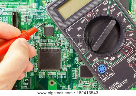 Digital multimeter and engineer's hand with probe on the circuit board background