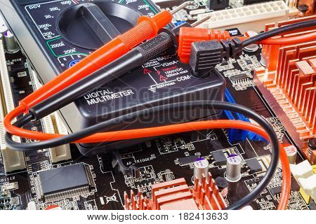 Digital multimeter with red and black probes on the computer motherboard closeup