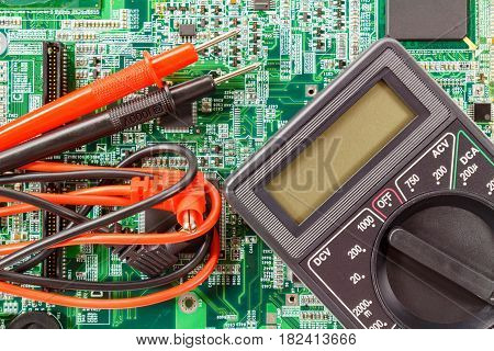 Digital multimeter with probes on a printed circuit board