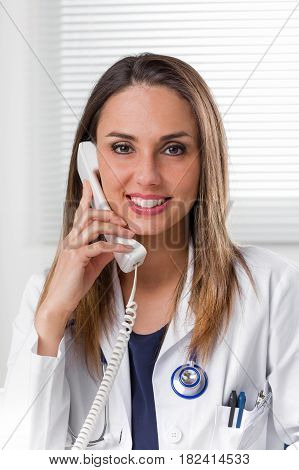Smiling Female Doctor With Telephone To Ear