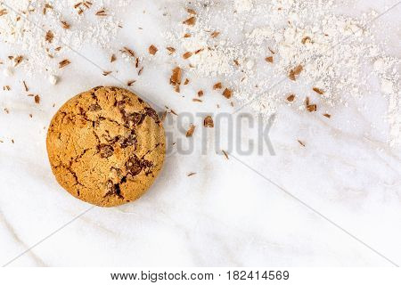 A photo of a crunchy chocolate chips cookie with chocolate shavings and flour around it, shot from above on a white marble background, with copyspace