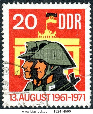 GERMANY - CIRCA 1971: A stamp printed in Germany (GDR) dedicated to 10 years of Berlin Wall shows the Militiaman Soldier and Brandenburg Gate circa 1971