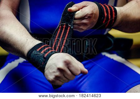 closeup of hands athlete powerlifter in wristbands