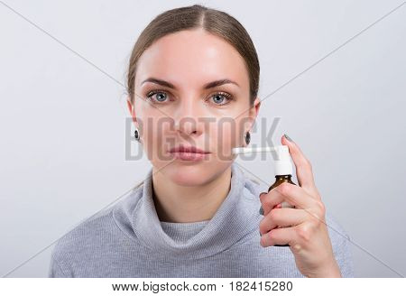 Attractive girl taking a medicine with spray inside the throat on light background. Throatache. Healthcare concept.