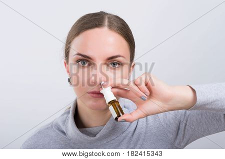 Attractive girl taking a medicine with spray inside the nose on light background. Nasal congestion. Healthcare concept.