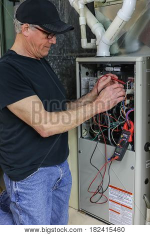 Furnace Repairman Servicing High Efficiency Gas Heating Unit