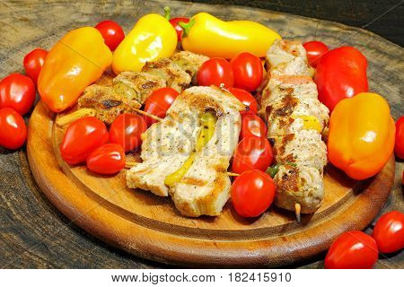 Grilled meat kebabs with vegetables on a wooden board