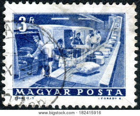 HUNGARY - CIRCA 1964: A stamp printed in Hungary shows a loading parcels circa 1964