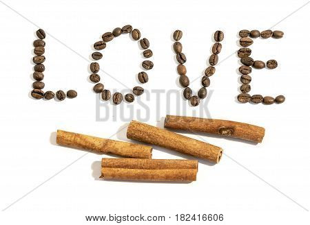 The word love written with cinnamon stick and coffee beans on white background