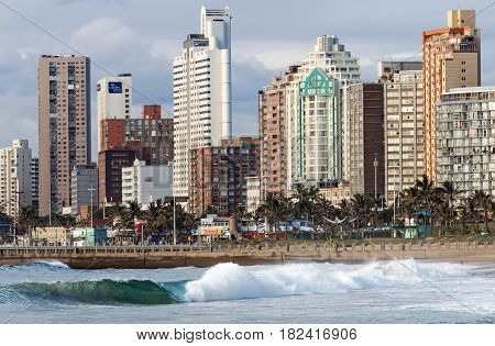 People On Early Morning Beach Against City Skyline