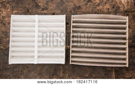 Close up used and new air filter of car on dirt background.