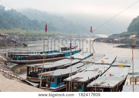 Pakbeng, Laos - Mar 04 2015: Slow Boats At Mekong River In Pakbeng Village. The Village Is The Major