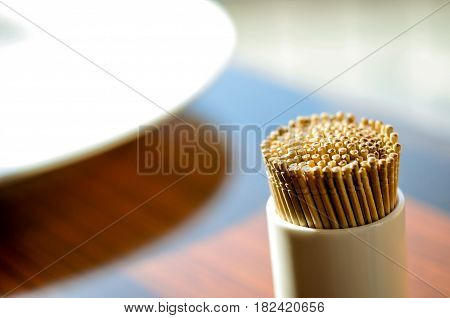 Toothpicks. Many toothpicks in the ceramic bottle on the wooden table.