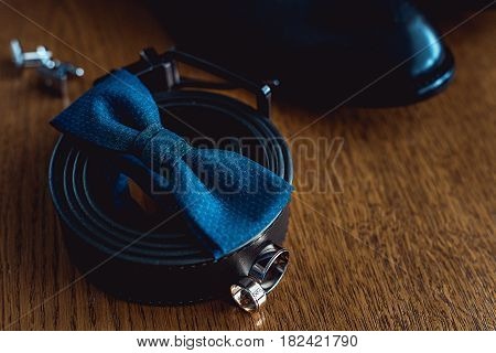 Close up of modern man accessories. Blue bowtie, leather shoes, belt, cufflinks and wedding rings.