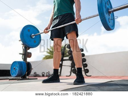 Weightlifting fitness man bodybuilding or powerlifting at outdoor gym. Bodybuilder strength training lifting barbell weights doing deadlift exercise.