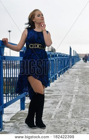 Elegant young fashion frozen woman in dress on bridge at winter season