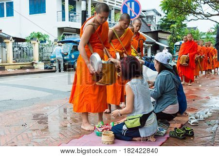 Luang Prabang, Laos - Jun 12 2015: Buddhist Alms Giving Ceremony In The Morning. The Tradition Of Gi