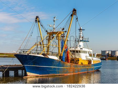 Modern Dutch trawler moored at a wooden jetty in a fishing port