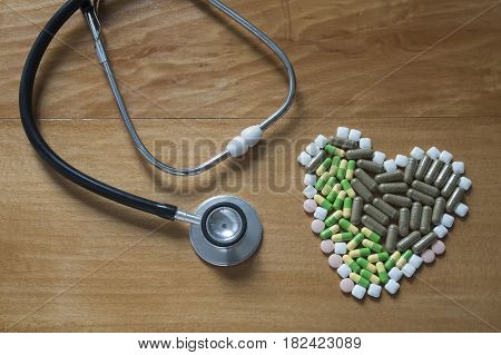 Black Stethoscope and pill on wood table