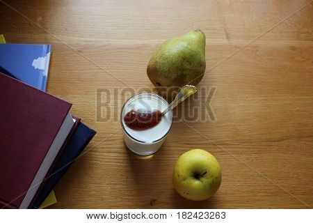 Books with morning yogurt on the table. Fresh yogurt with fruits on the table. Quick snack between lessons.
