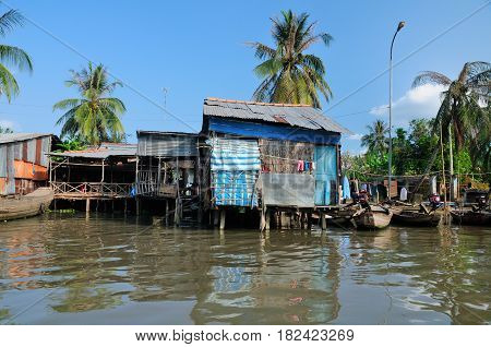 Small shacks on the mekong river in Vinh Long south vietnam on a sunny blue sky day.