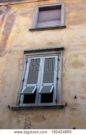 typical beautiful Italian shutters with vents on yellow wall